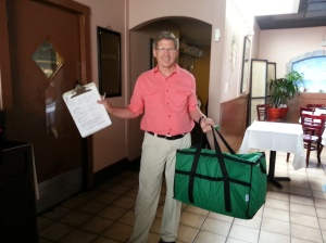 A food runner carries an insulated bag for cold food and a form to track this food donation's time and temperature.