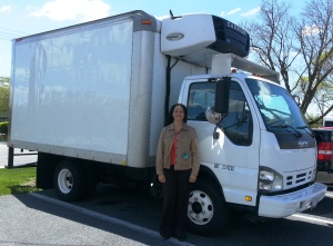 Pat at Rainbow Community Development Center stands next to her truck with a new lift gate