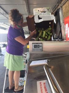 Jessica Weiss loads food scraps into the BIOGAS food composter